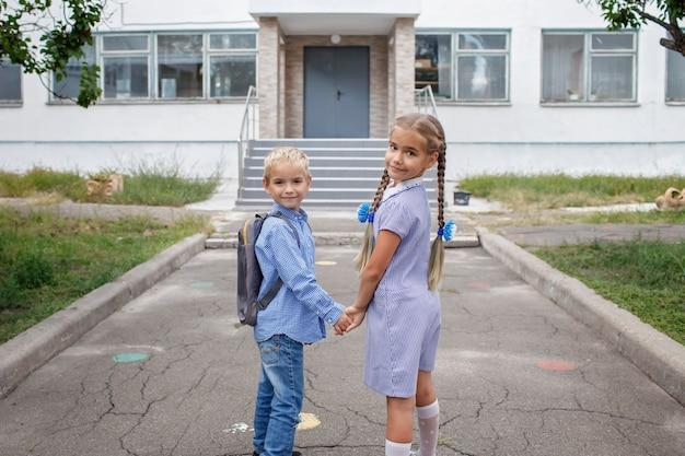 Снова в школу братья и сестры с рюкзаками, стоящие у дверей школы до их первого дня офлайн.