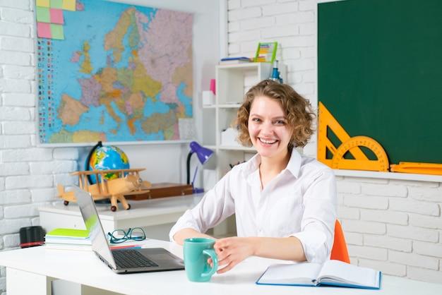 学校に戻って笑顔の女性教師の教育知識と学習の概念