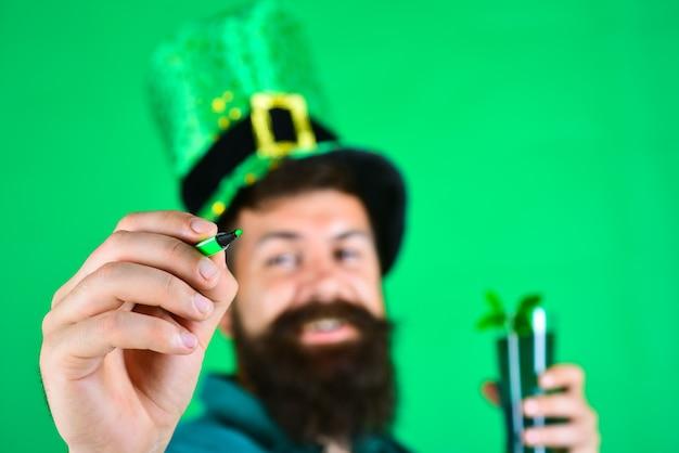 学校に戻る聖パトリックの日は、緑のマーカーでレプラコーンの帽子をかぶった幸せな男の肖像画をクローズアップ