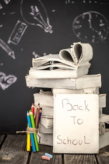 学校に戻って、本のスタックとチョーク、教育概念で描かれた黒板背景に学用品