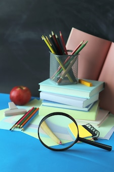 学校に戻る、本の山、虫眼鏡、テーブルの上の文房具