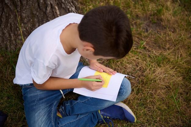 学校に戻る。夏休みから新学期が始まります。初日の授業の合間に宿題をしている小学生の可愛いハンサムな男子生徒の俯瞰図