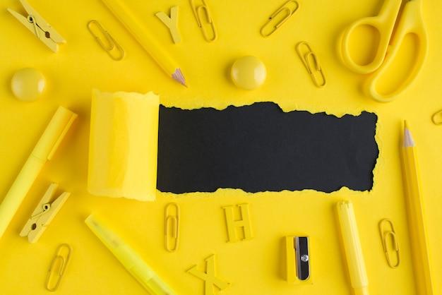 개학 편지지 개념입니다. 오버헤드 뷰 위의 노란색 편지지와 카피스페이스가 있는 검정 배경 위에 찢어진 밝은 노란색 종이의 클로즈업 사진