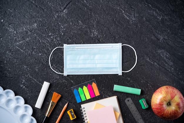 Вернуться к концепции дизайна школьника, вид сверху канцелярских принадлежностей на фоне черной шиферной таблицы с копией пространства.