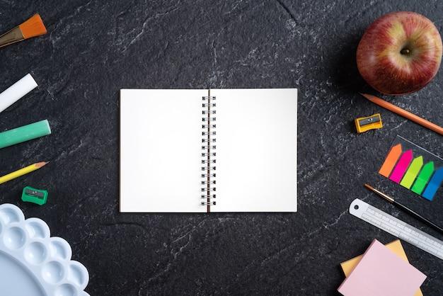학교 학생 디자인 개념으로 돌아가서, 복사 공간이 있는 슬레이트 블랙 테이블 배경 위에 있는 문구류의 상단 보기.