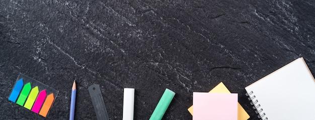学校の学生のデザインコンセプトに戻る、コピースペースとスレートの黒いテーブルの背景上の文房具の上面図。