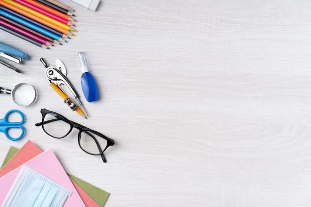 Вернуться к концепции дизайна школьника, вид сверху канцелярских принадлежностей на фоне деревянного стола с копией пространства.