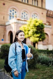 バックパックを身に着けている本とメモ帳を保持している公園の側に探している学校の学生の女の子に戻る。