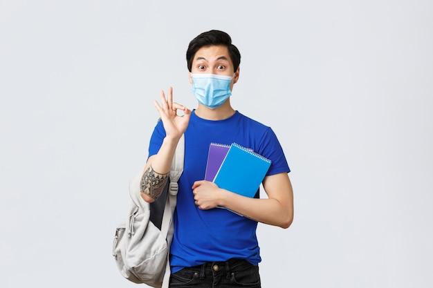 学校に戻り、covid-19、教育、大学生活のコンセプトで勉強します。すべて管理下にあります。医療マスクのハンサムなアジアの男性学生は大丈夫のサインで問題を保証しません、クラスに向かいます