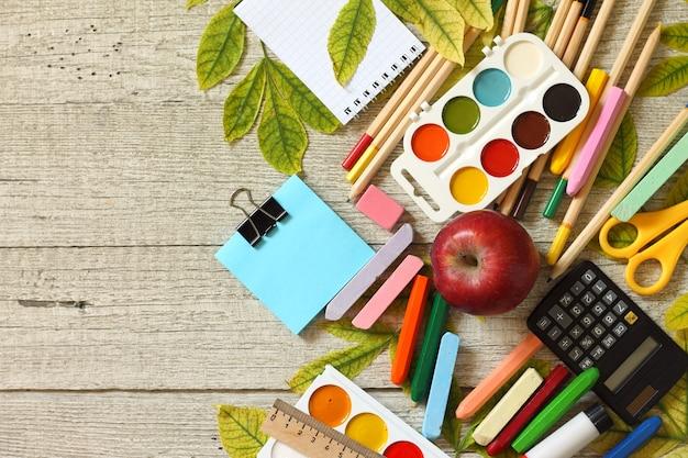 紅葉とさまざまな学用品の文房具で学校のテーブルに戻る