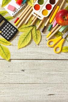 Снова в школу стол с осенними листьями и школьными принадлежностями свободное место для текста