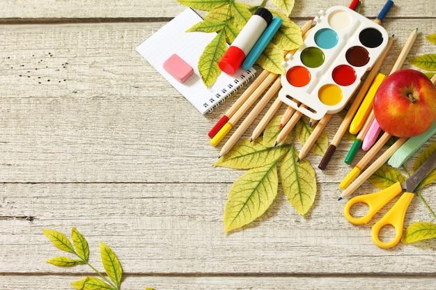 Снова в школу стол с осенними листьями, яблоком и школьными принадлежностями