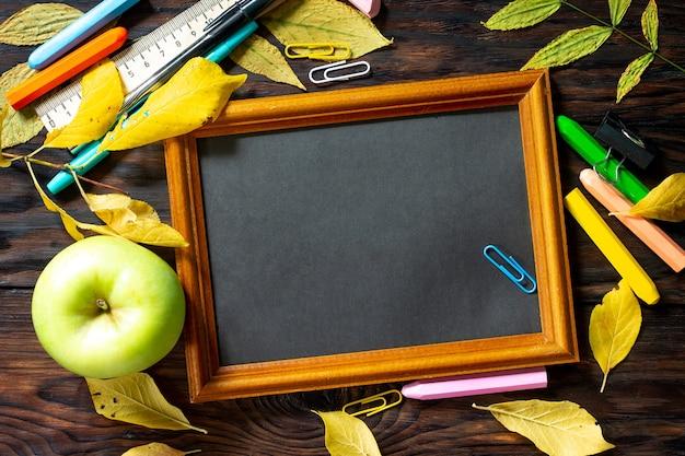 Снова в школу стол с осенними листьями, блокнот, яблоко и школьные принадлежности