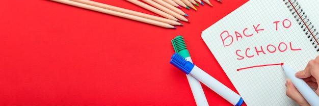 다시 학교로 아이는 시작의 개념을 빨간색 마커로 공책에 다시 학교에 씁니다.