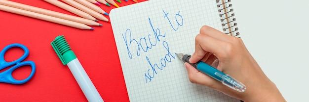 학교로 돌아가다. 아이는 학년 초의 개념을 만년필로 공책에 씁니다. 학교 용품 세트인 빨간색 배경에 있는 사이트의 배너입니다.