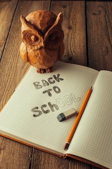 Обратно в школу, концепция воспитания детей. сова на деревянном столе.