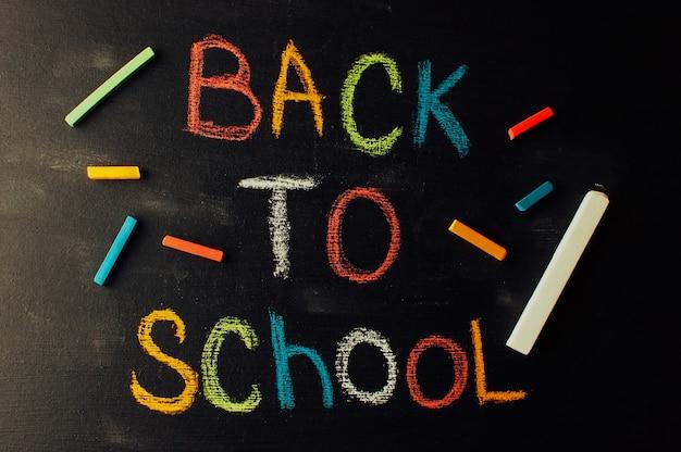 Снова в школу, концепция воспитания детей. надпись на доске цветным мелом.