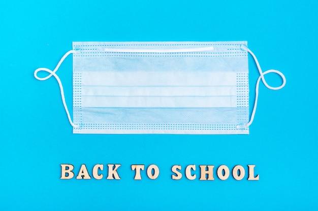 Обратно в школу. надпись деревянными буквами и защитная медицинская маска на синем фоне