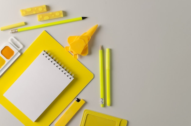 学校に戻る。トレンドはグレーに黄色です。灰色の背景に学校の文房具。鉛筆、消しゴム、ノート、ペンキ、鉛筆削り-オフィスの黄色の商品。