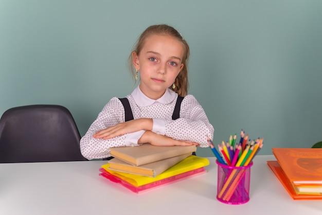 학교로 돌아가서 책상에 앉아 숙제를 하는 노트북에 그림을 쓰는 생각하는 소년