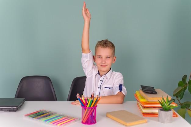 Обратно в школу думающий мальчик пишет рисунок в блокноте, сидя за столом и делает домашнее задание