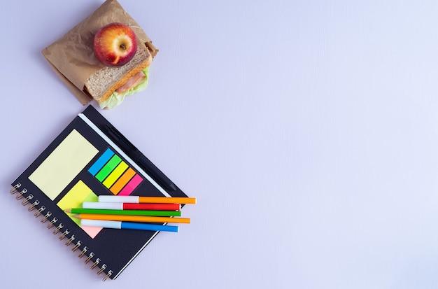 Обратно в школу с тетрадью, карандашами и бутербродом с фруктами. скопируйте пространство.