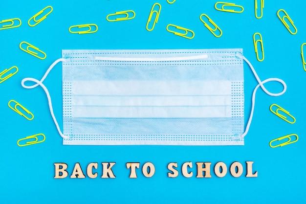 Обратно в школу. деревянные надписи и защитная медицинская маска в окружении скрепок на синем фоне