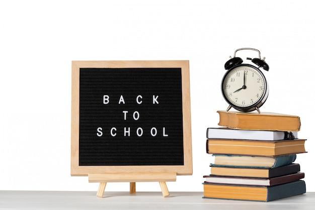 本と孤立した白地にビンテージの目覚まし時計が付いているレターボード上の学校の言葉に戻る