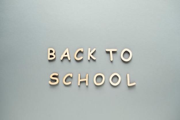 Снова в школу слова, написанные деревянными буквами на сером