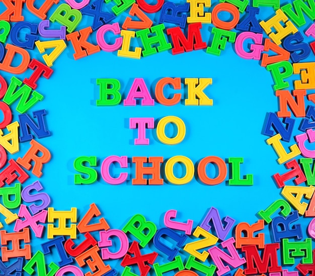 青い背景にプラスチックのカラフルな文字で書かれた学校に戻る
