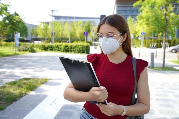 学校に戻る。眼鏡とffp2保護マスクを持った若い女性は、学校に入る前にレッスンを確認します。