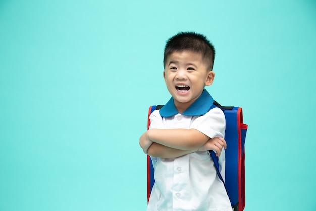 Веселый улыбающийся азиатский маленький мальчик в школьной форме с рюкзаком, с удовольствием на зеленой стене, первый день детского сада и концепция back to school