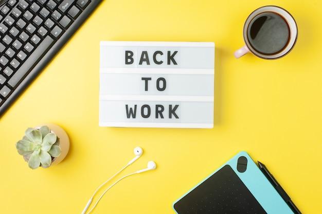 仕事に戻る-黄色の背景の職場のディスプレイライトボックスのテキスト。黒のキーボード、白のイヤホン、コーヒー、タブレット。