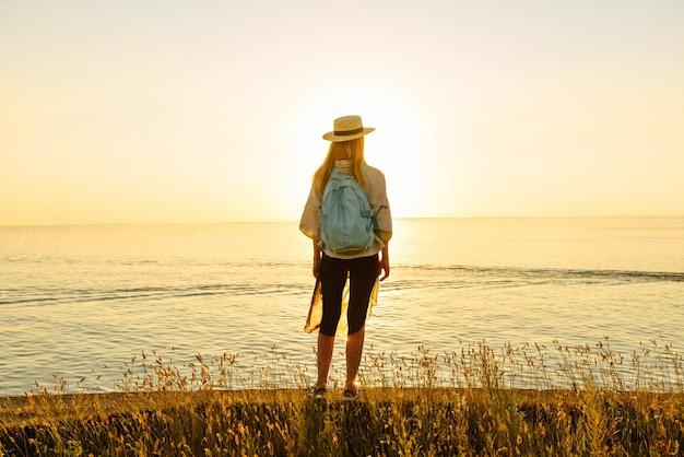 배낭을 메고 돌아오는 관광 여성은 해질녘 바다의 아름다운 전망을 바라보고 있습니다. 여행 및 모험 개념