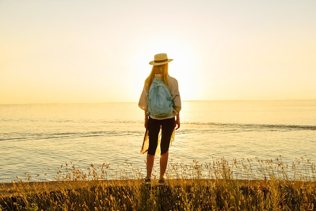Back tourist woman with backpack looks at the beautiful view of the sea at sunset. travel and adventure concept