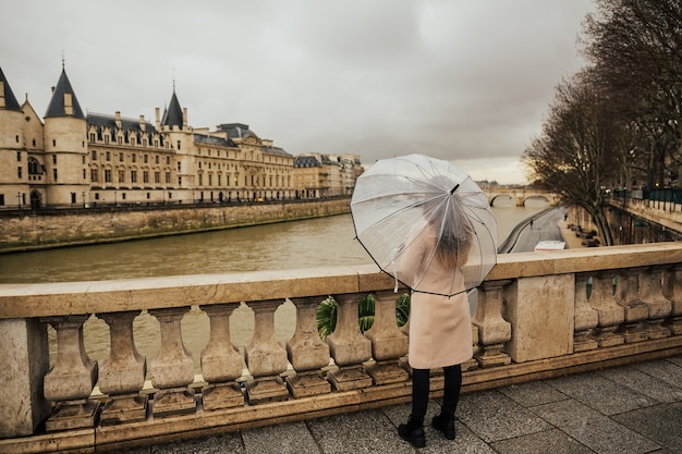 Back of traveler young girl walking in paris in the rain day and holds transparent umbrella in his hand.