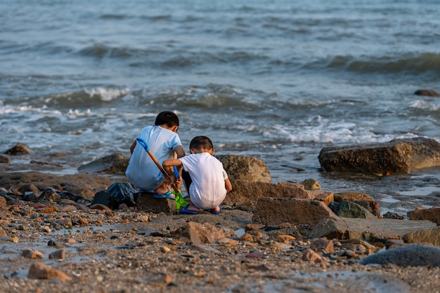 The back of two children playing upstream of the beach.