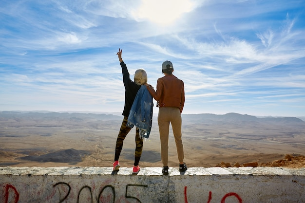 The back of two women, stand with their hands up overlooking the mountains.