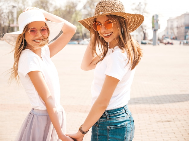 Back of two young beautiful blond smiling hipster girls in trendy summer white t-shirt clothes and hat.  . couple holding each other hands