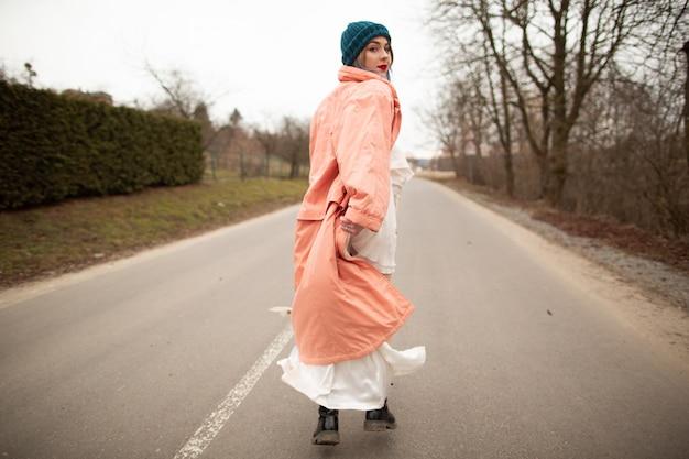 По дороге едет женщина в красивом пальто и белом платье, back viev