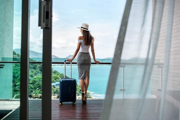 후면보기 : 모자에 고급스러운 인물이있는 아름다운 관광객은 바다와 산의 아름다운 전망을 제공하는 수하물 발코니와 함께 포즈를 취합니다. 여행 및 휴가.