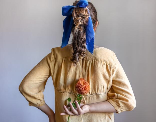Вид сзади девушка держит цветок хризантемы за спиной на сером фоне