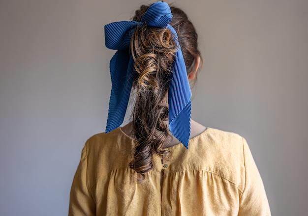 회색 배경에 머리에 활이 달린 드레스를 입은 소녀의 뒷모습
