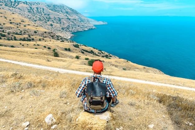 뒷모습 배낭을 메고 산 꼭대기에 앉아 아름다운 바다를 바라보는 남자. 여름 여행 개념입니다.
