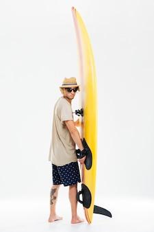 다시 서핑 보드를 들고 흰 벽에 고립 된 그의 어깨 너머로보고 젊은 서퍼보기