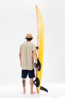 다시 흰 벽에 고립 된 서핑 보드를 들고 젊은 서퍼보기