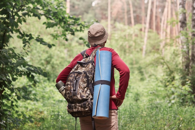 Back view of active backpacker looking for way out in forest, having sleeping pad and dark rucksack with thermos at his back, enjoying active holidays, stick to travel lifestyle. travel concept.