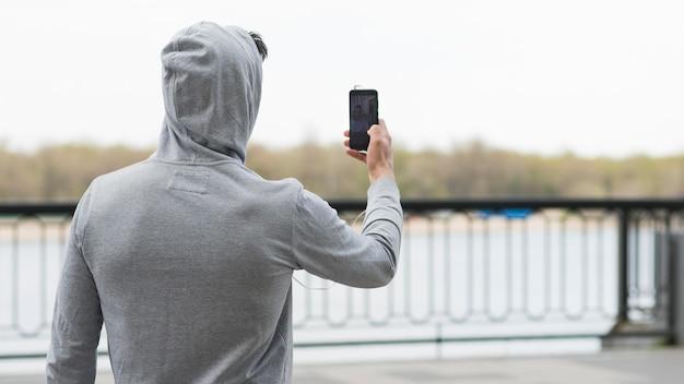 写真を撮る大人の男性の背面図