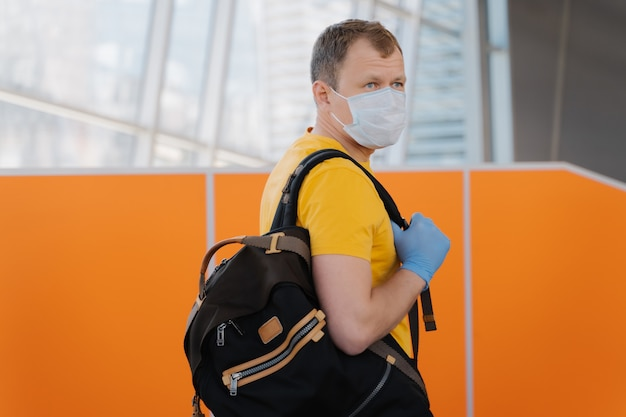 Back view of adult man carries rucksack, wears medical face mask and rubber gloves, prevents from coronavirus and epidemic disease