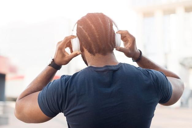 Vista posteriore uomo afroamericano che ascolta la musica tramite le cuffie
